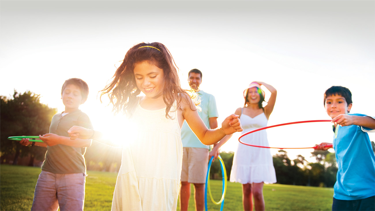 A girl with long brown hair and yellow dress stands in the sunlight in front of her family holding hula hoops in a field.