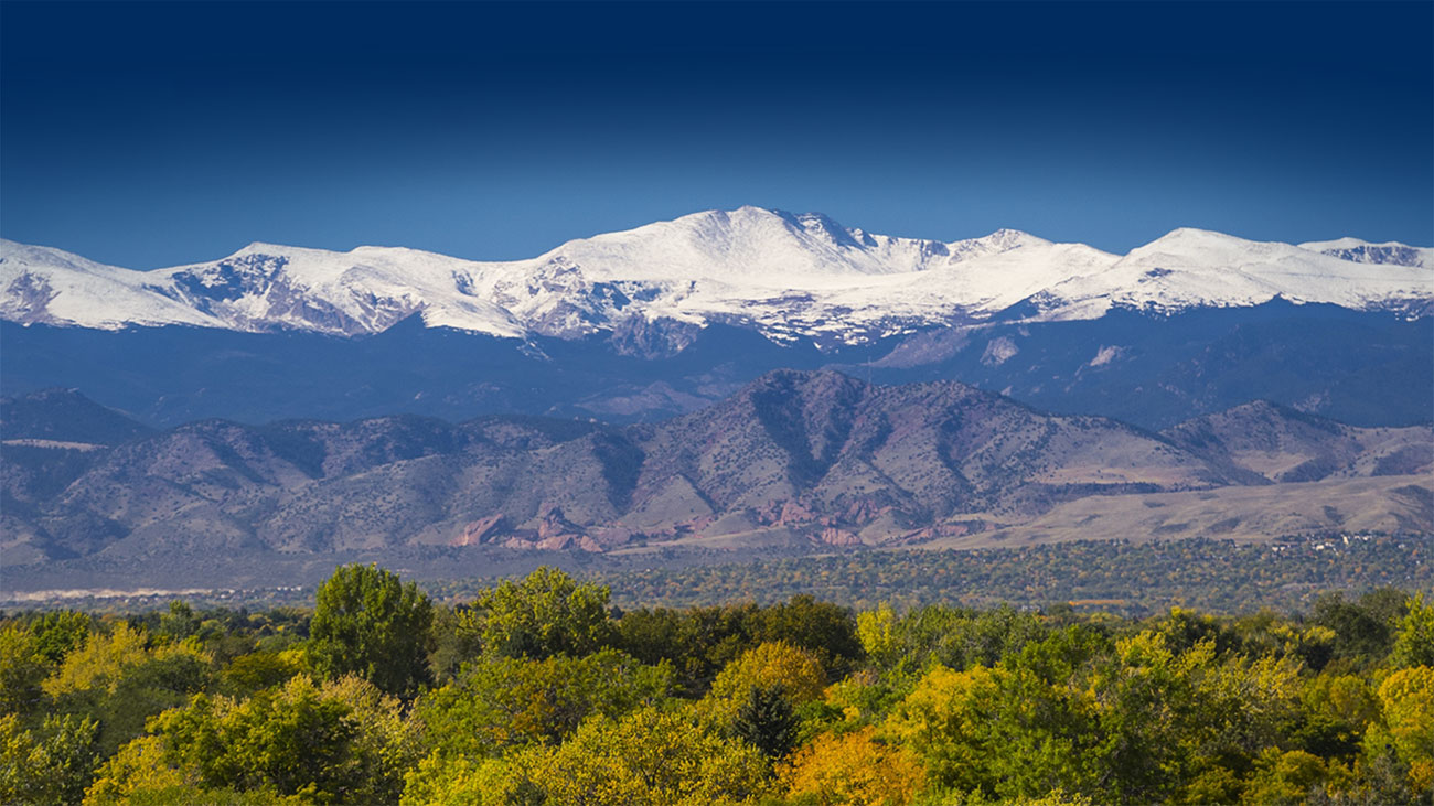A view of the Rocky Mountains with snow-capped mountains, green and brown foothills and bright green trees in the valley.